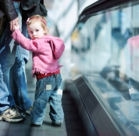 Young girl on escalator holding adults hand