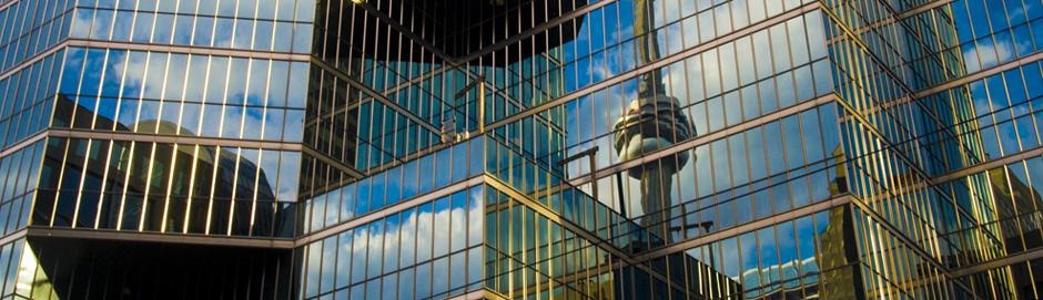Image of a glass building with the blue sky, clouds, and the CN Tower reflected in it