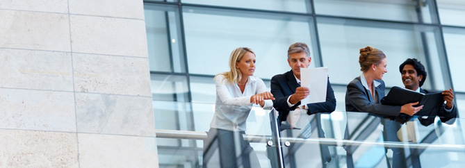Image of four adults in business attire leaning over a glass railing collaborating and looking at paper